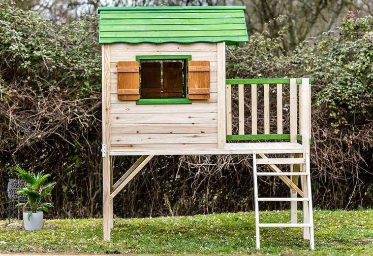cabane en bois FSC montée sur pilotis verte et marron avec balcon